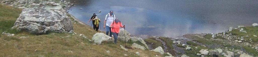 Senderistes caminant pel costat del llac de Mainera